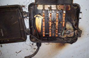 Un boîtier ouvert avec connexion détériorée.
