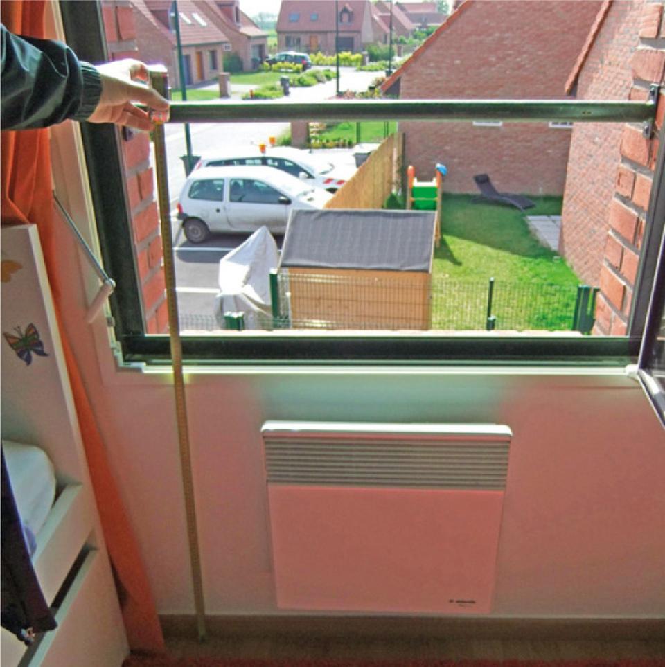 Fenêtre avec un garde-corps métallique (lisse) dont l'espacement réglementaire des éléments de protection n'est pas respecté