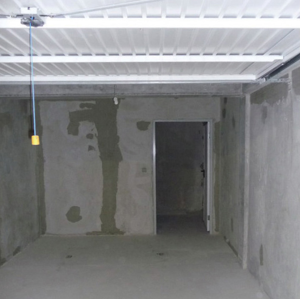 Cave installée en fond de box dans un parc de stationnement couvert, ce qui est interdit