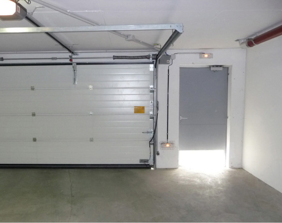 Porte piéton d'un parking couvert avec ouverture par le bas au lieu de par le haut