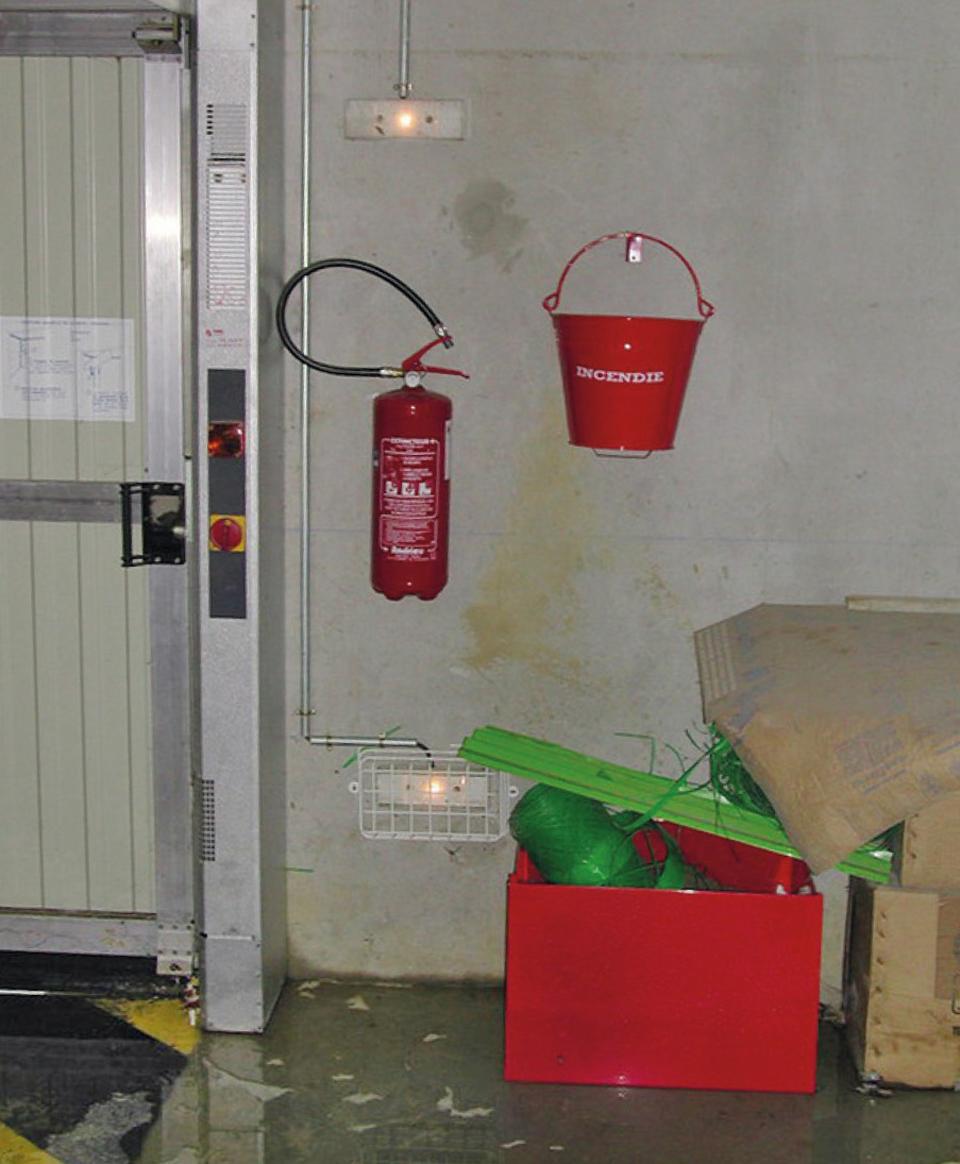Le bac contenant la réserve à sable contre incendie est rempli de déchets et inaccessible