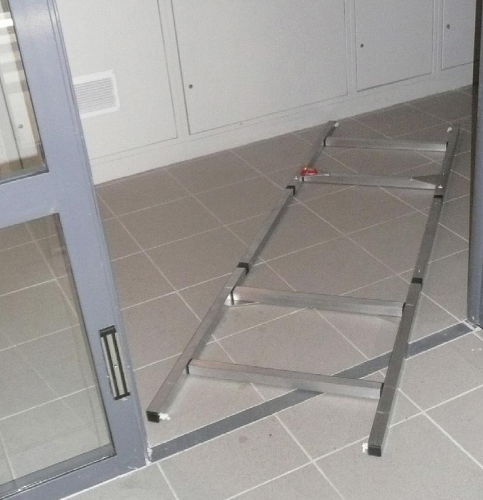 Brancard déposé sur le sol afin de vérifier son passage entre une porte et un couloir d'un bâtiment d'habitations collectives
