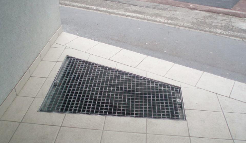 Grille EP (eaux pluviales) avec un maillage supérieur à 2 cm, entravant le cheminement extérieur d'un parking