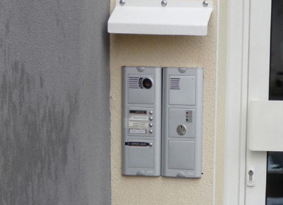 Commande de portier mal implantée, à moins de 0,40m de l'angle avec le mur perpendiculaire, non conforme aux règles d'accessibilité NRH