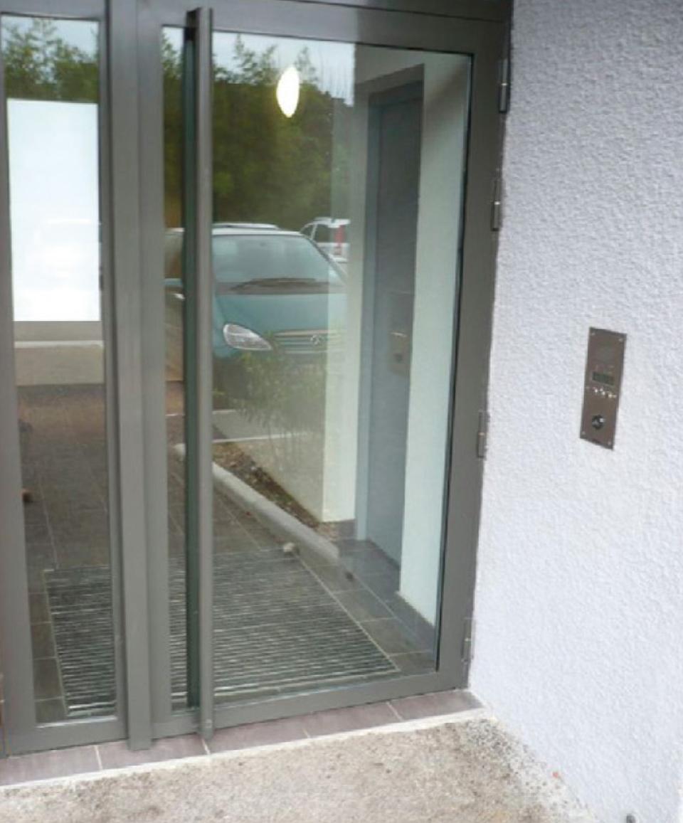 Porte d'entrée vitrée d'un bâtiment sans marquage visuel, difficilement repérable par les personnes déficientes visuelles