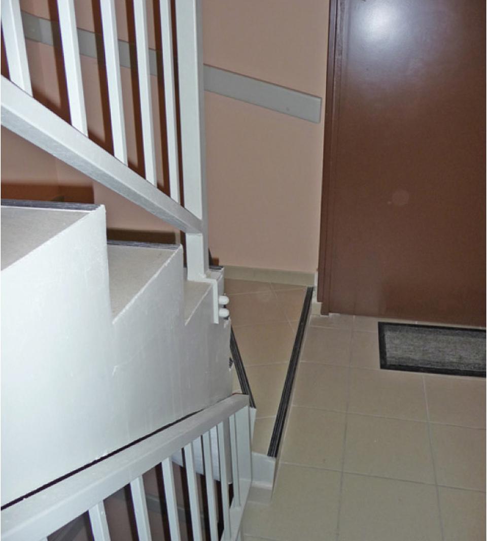 Mauvaise implantation d'une porte palière, ne permettant pas le prolongement de la main courante de l'escalier.