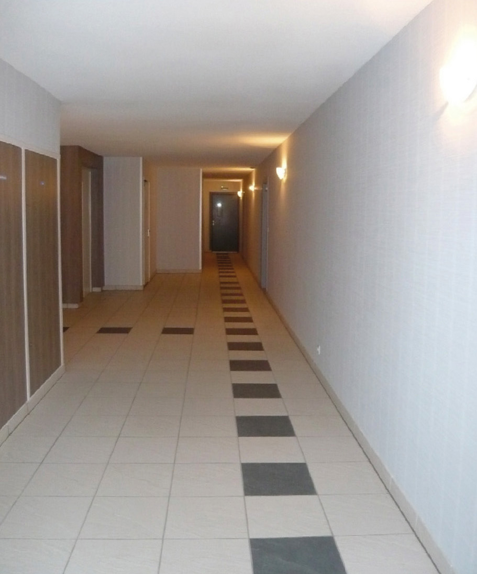Partie commune intérieure à un bâtiment : absence de revêtement acoustique absorbant au sol et défaut d'éclairage